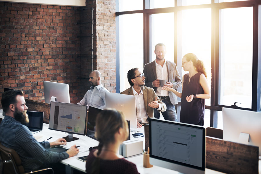Cyber Liability - Group of Employees Using Computers in their Brick Office