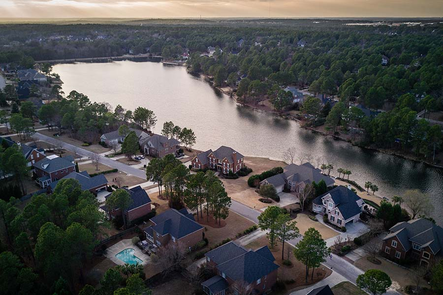 Insurance Quote - Aerial View of a Residential Neighborhood in North Carolina By the Lake with Luxury Homes at Sunset