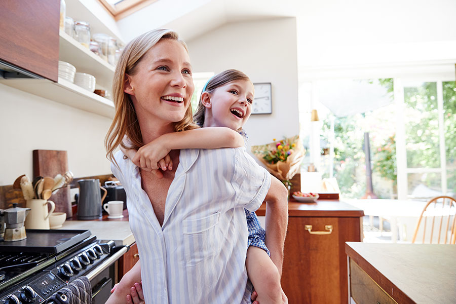 Personal Insurance - Closeup Portrait of a Cheerful Young Mother Standing in the Kitchen While Giving a Piggyback Ride to Her Daughter